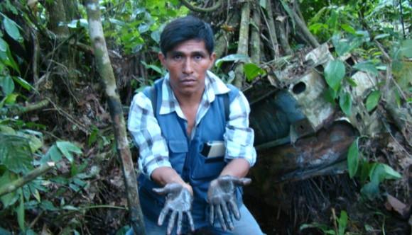 Cuenca del Pastaza. Monitor Ambiental de la Federación Indígena Quechua del Pastaza - FEDIQUEP muestra con sus propias manos la evidencia de la contaminación expuesta en el bosque. Abril, 2013.