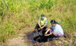 Cuenca del Tigre. Monitor ambiental y madre indígena de la Federación de Comunidades Nativas del Alto Tigre - FECONAT, ante un punto contaminado con petróleo. Año 2012.
