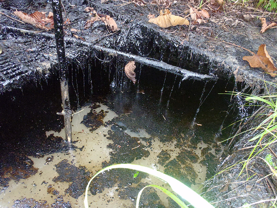 Foto de pozo con presencia de hidrocarburos a superficie abierta.